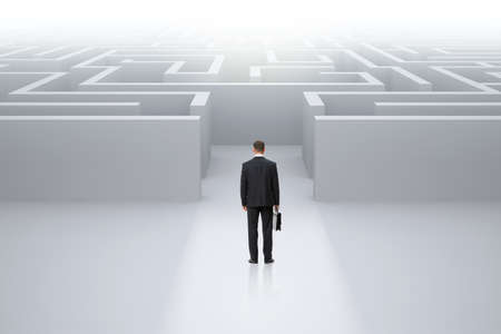 Full-length backview portrait of businessman with case standing in front of maze. Concept of leadership and difficulties Stock Photo