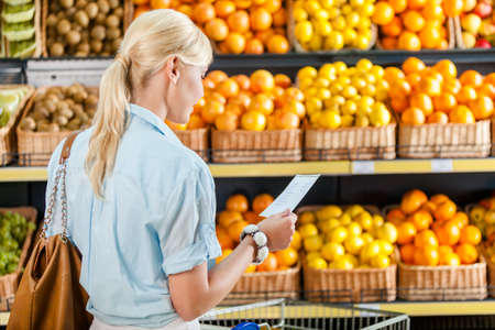 Girl looks through shopping list near the pile of fruits lying in the braided baskets in the store Stock Photo