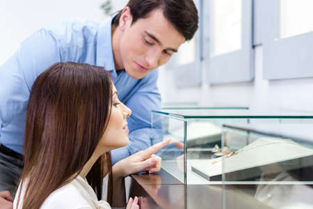 jewel case: Girl with male selects expensive jewelry at jewelers shop. Concept of wealth and luxurious life