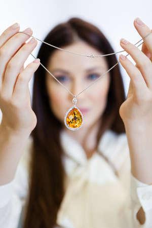 caras emociones: Mujer que sostiene el collar con zafiro amarillo en la tienda del joyero. El concepto de riqueza y vida de lujo Foto de archivo