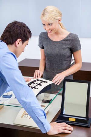 Man choosing engagement ring at jewelers shop. Concept of wealth and luxurious life photo