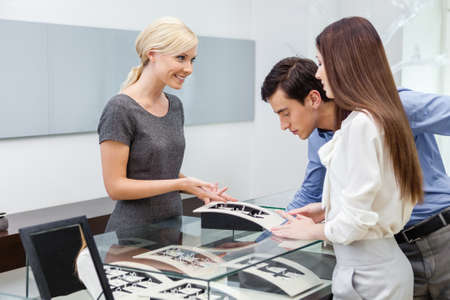 Salesperson helps couple to select jewelry at jewelers shop. Concept of wealth and luxurious life photo