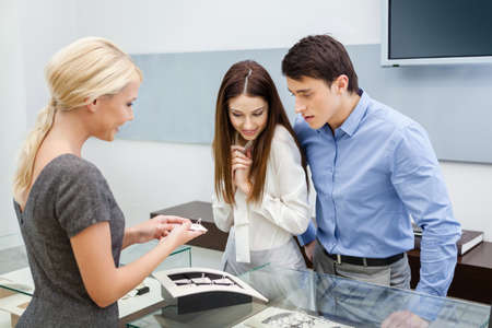 Salesperson helps couple to choose jewelry at jewelers shop. Concept of wealth and luxurious life photo