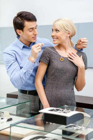 platinum hair: Young man puts necklace on his girlfriend at jewelers shop. Concept of wealth and luxurious life