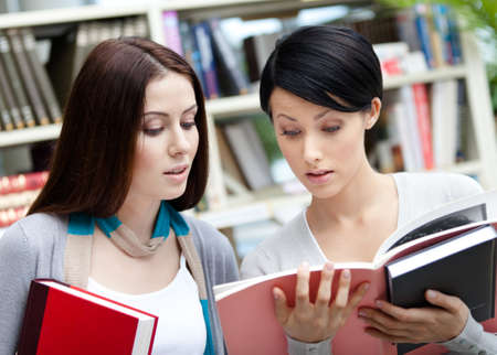 Two young female students read books at the library