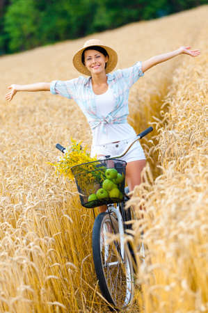 Woman pedals bicycle with apples and flowers in rye field. Concept of rural lifestyle and sport photo