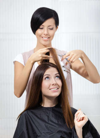 Hair stylist cuts hair of woman in hairdressing salon. Concept of fashion and beauty Stock Photo