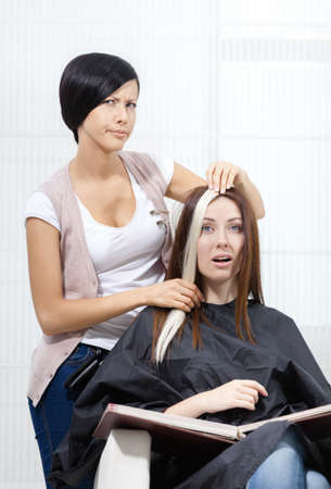 doubtfulness: Hair stylist tries lock of dyed blond hair on the client sitting on the chair in the hairdressers