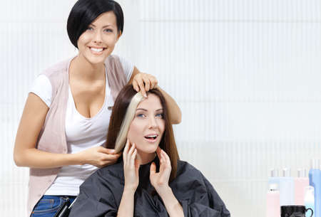 horizontal haircut: Hairdresser tries lock of dyed blond hair on the client sitting on the chair in the hairdressing salon Stock Photo