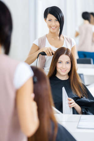 hairdress: Reflection of hair stylist doing hair style for woman in hairdress salon. Concept of fashion and beauty