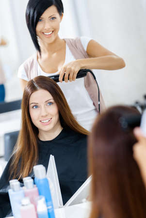 hairdress: Reflection of hairdresser doing hair style for woman in hairdress salon. Concept of fashion and beauty
