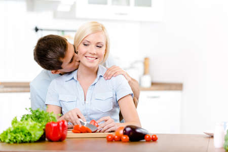 Man kisses woman while she is cooking sitting at the kitchen table full of vegetables photo
