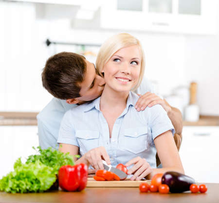 Man kisses lady while she is cooking sitting at the kitchen table full of groceries photo