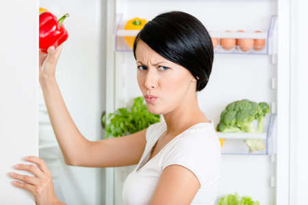 Woman takes bell pepper from the opened fridge full of vegetables and fruit. Concept of healthy and dieting food photo