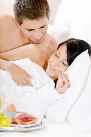 Liegen Mann serviert Frau Fr�hst�ck im Bett. Konzept der Liebe und Zuneigung photo