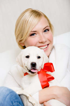 Woman embracing white white puppy with red ribbon on the neck photo
