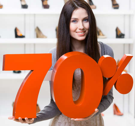 Woman keeps the model of 70% sale on footwear standing at the shopping center against the showcase with pumps photo