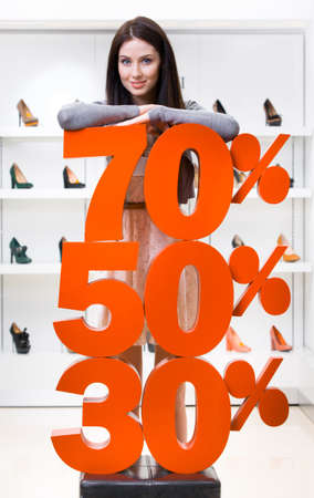 high heeled shoe: Woman showing the percentage of sales on high heeled shoes in the shopping center against the window case with footwear Stock Photo