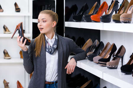 heeled: Woman with shoe in hand chooses high heeled shoes looking at the shelves with numerous heeled shoes