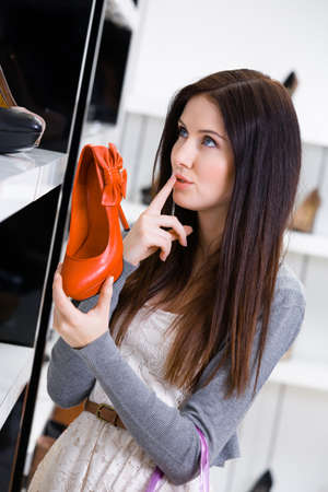 Woman keeping a pump at the shop cant decide what to buy photo