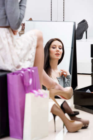 Reflection of woman sitting on chair and trying on new pumps in the shop photo
