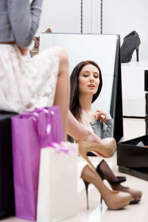 comprando zapatos: Reflexión de la mujer sentada en la silla y tratando sobre las nuevas bombas en la tienda Foto de archivo