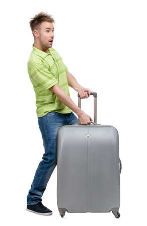 heave: Full-length portrait of man who lifts silver suitcase, isolated on white. Concept of traveling and cool vacations Stock Photo