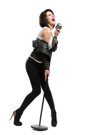 Full-length portrait of rock musician wearing leather jacket and handing static mic, isolated on white. Concept of rock music and rave photo