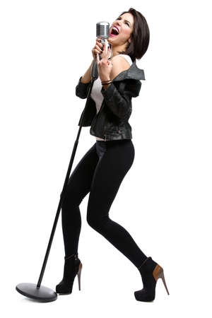Full-length portrait of rock singer wearing leather jacket and keeping static microphone, isolated on white. Concept of rock music and rave photo