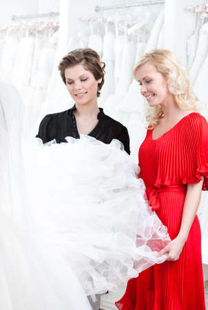 Two girls stare at the wedding dress hesitating about fitting. White background photo