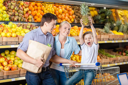 Family against shelves of fruits goes shopping. Father keeps a packet with fruits and vegetables, son hands pineapple photo