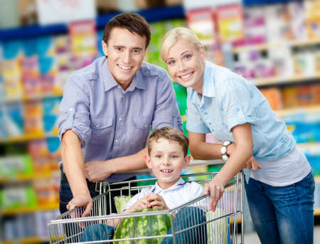 Family drives shopping trolley with food and boy sitting there with watermelon. Concept of fresh and healthy food and consumerism photo