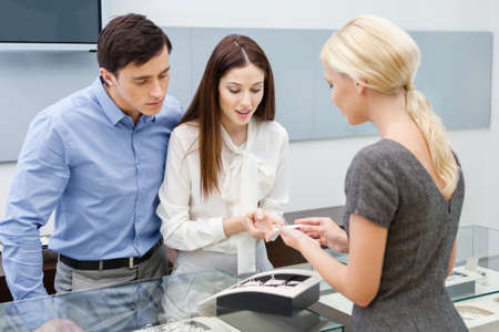 helps: Consultant helps couple to choose jewelry at jewelers shop. Concept of wealth and luxurious life Stock Photo