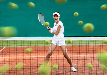 in action: Sports woman returning lots of balls at the tennis court. Concept of tournament preparation and healthy lifestyle Stock Photo