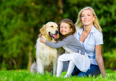 Mother and daughter with pet sitting on the grass at the summer park