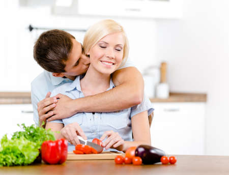 Man kisses female while she is cooking sitting at the kitchen table full of vegetables photo