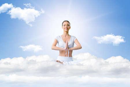 guardar silencio: Mujer joven en una posición de loto en el cielo durante la meditación