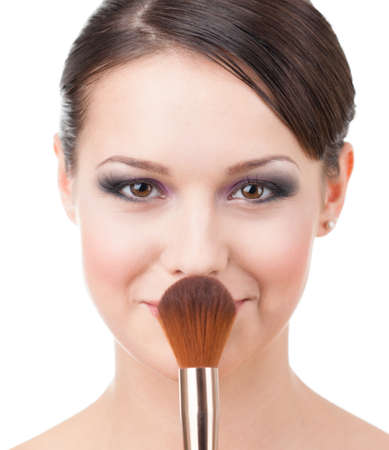 Pretty woman with cosmetic brush for powder, isolated on white photo