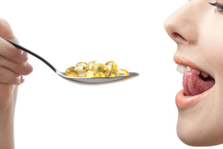 Close up of woman taking vitamins on the spoon, isolated on white. Cold remedy photo