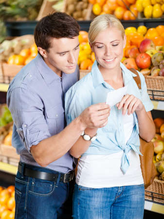 decides: Couple with shopping list against the heaps of fruits decides what to buy Stock Photo
