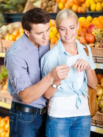 decide: Pareja con lista de la compra contra los montones de frutas decide qu� comprar Foto de archivo