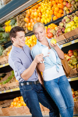 decides: Couple with shopping list against the piles of fruits decides what to buy Stock Photo
