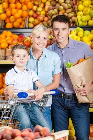Happy family against shelves of fruits goes shopping. Father keeps a packet with fruits and son sits in the cart photo