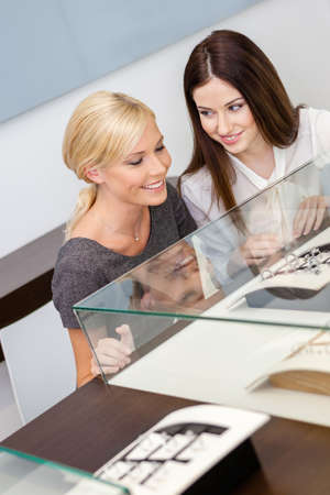 platinum hair: Two girls looking at window case with jewelry at jewelers shop. Concept of wealth and luxurious life