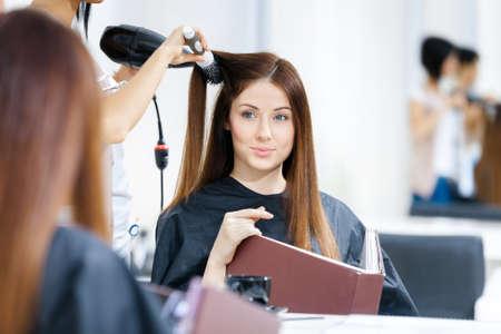secador de pelo: Reflexión de la peluquería haciendo corte de pelo para la mujer en la peluquería. Concepto de moda y belleza
