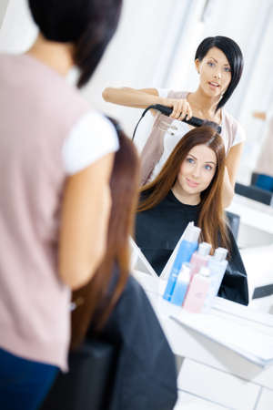 haircutter: Reflection of hairdresser doing haircut for woman in hairdress salon. Concept of fashion and beauty