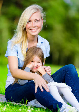Young mother and daughter sitting on the grass embrace each other. Leisure time of happy family photo