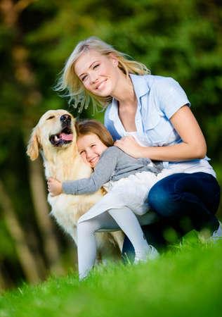 mujer con perro: Madre e hija con el perro perdiguero de oro que se sienta en la hierba y abrazando al perro en el parque de verano Foto de archivo