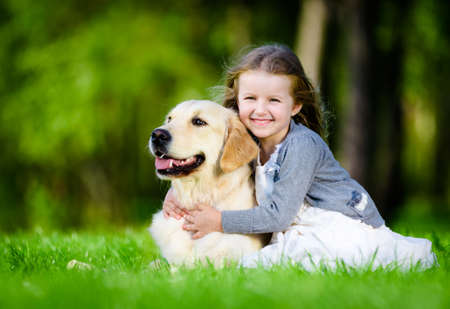 Little girl sitting on the green grass with labrador retriever in the summer park