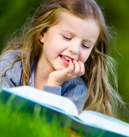Girl reads interesting book lying on the grass in the summer park photo